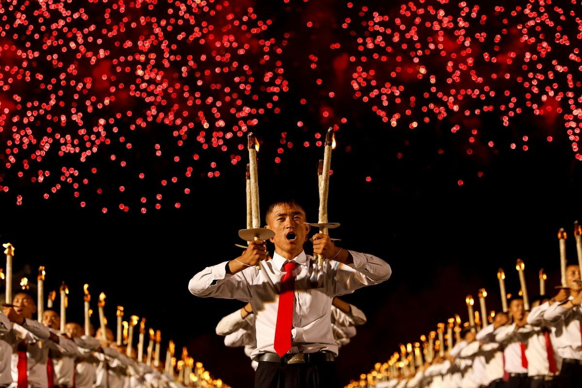 Fireworks exploding over participants carrying torches during a torchlight procession at the celebration marking the 70th anniversary of North Korea's foundation in Pyongyang, North Korea, on Sept 10, 2018.