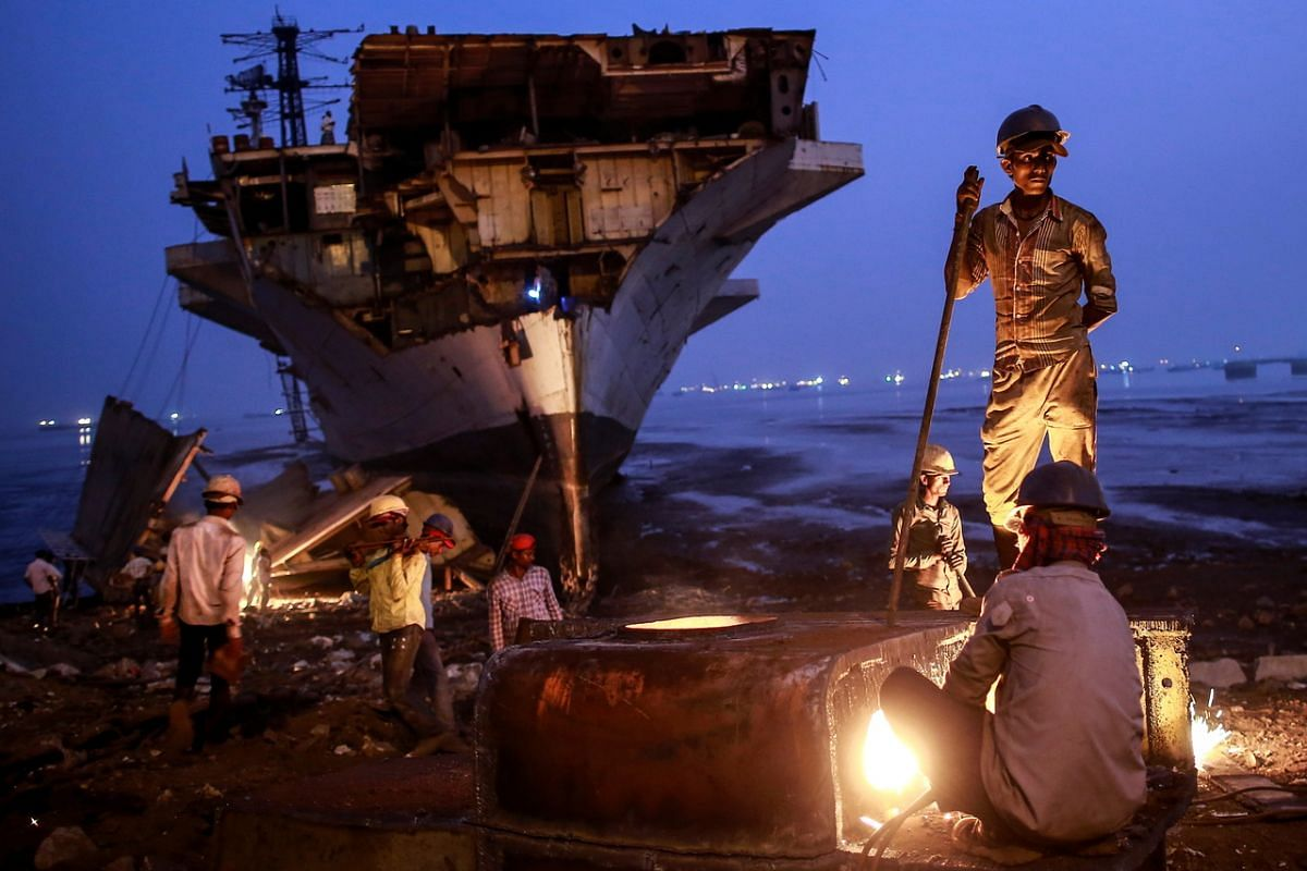Workers dismantling parts of decommissioned Indian Navy ship INS Vikrant at a ship breaking yard in Mumbai, on Nov 24, 2014.
