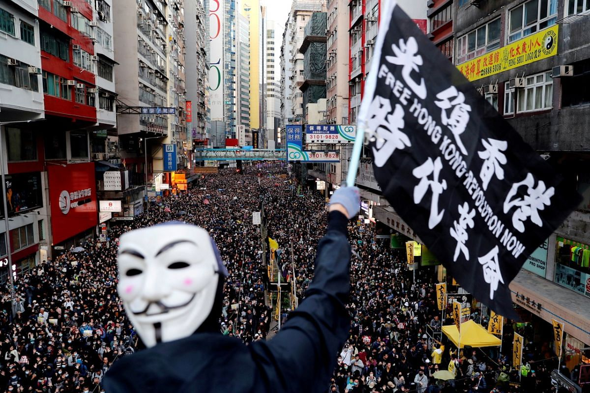 A protester wearing a Guy Fawkes mask waving a flag during a Human Rights Day march organised by the Civil Human Right Front, in Hong Kong, China, on Dec 8, 2019.