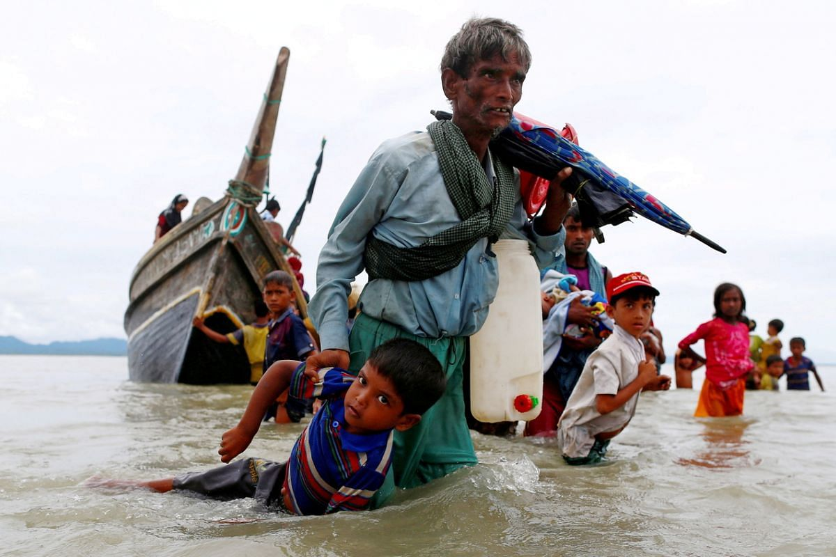 A Rohingya refugee pulling a child as they walk to shore after crossing the Bangladesh-Myanmar border by boat through the Bay of Bengal in Shah Porir Dwip, Bangladesh, on Sept 10, 2017.
