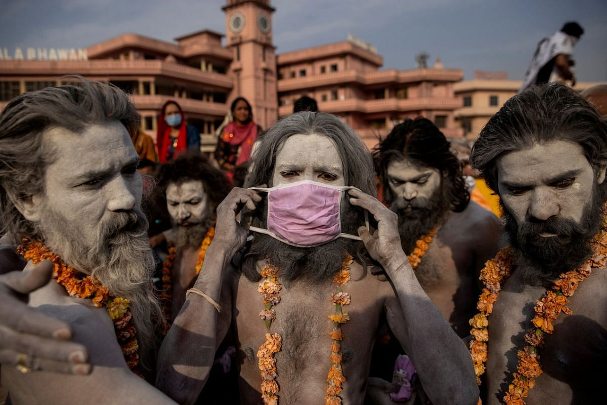 """A Naga Sadhu, or Hindu holy man, putting on a mask before the procession for taking a dip in the Ganges river during Shahi Snan at """"Kumbh Mela"""", or the Pitcher Festival, amid the spread of Covid-19, in Haridwar, India, on April 12, 2021."""