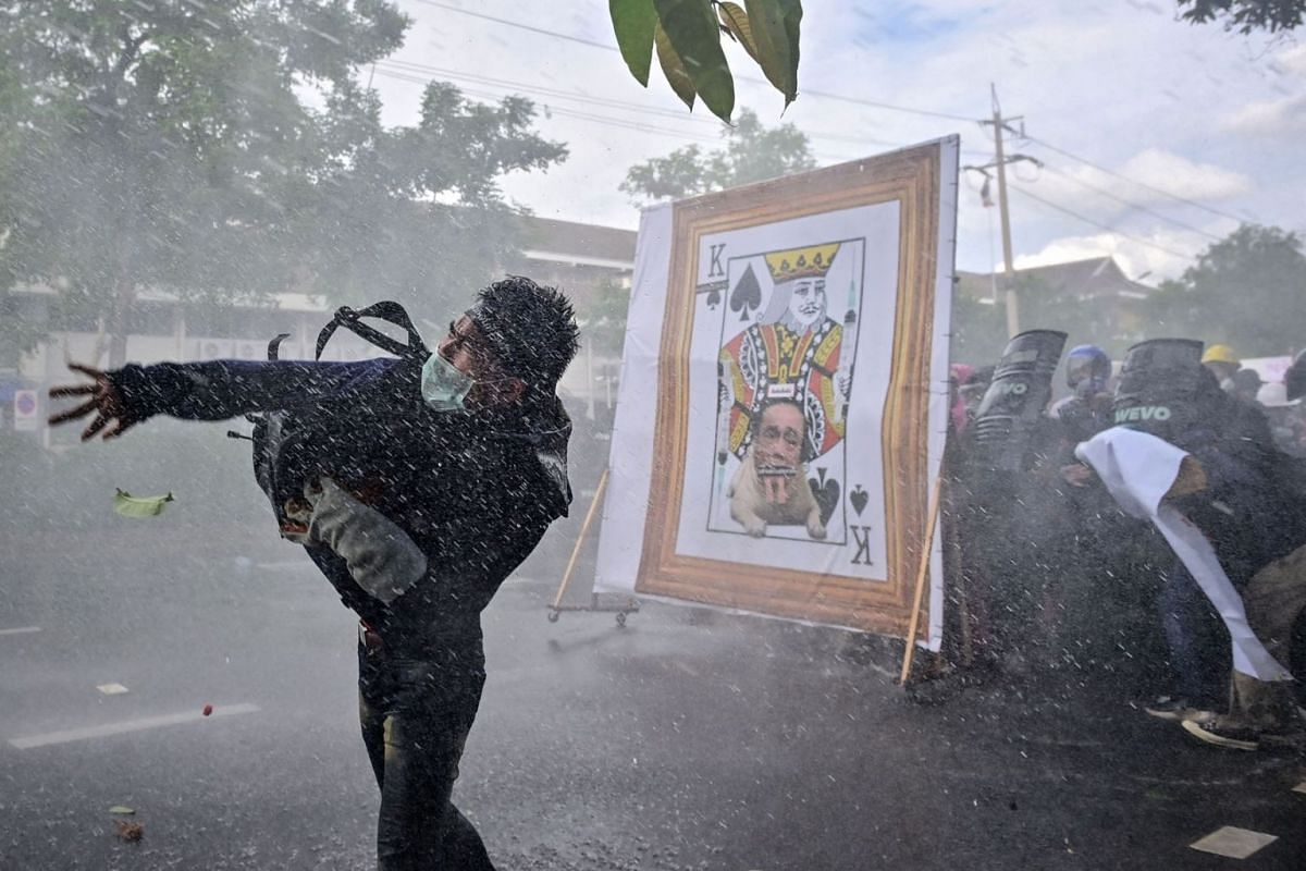 A pro-democracy protester throws an object as others take cover from police water cannon behind a derogatory image of Thailand's Prime Minister Prayut-Chan-O-Cha, as they march to Government House to call for his resignation in Bangkok on July 18, 20