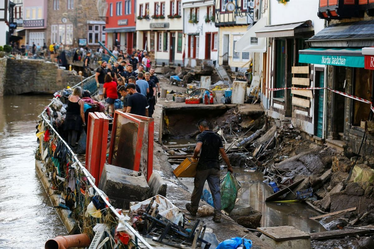 Police officers and volunteers clean debris in an area affected by floods caused by heavy rainfalls in Bad Muenstereifel, Germany, July 18, 2021.