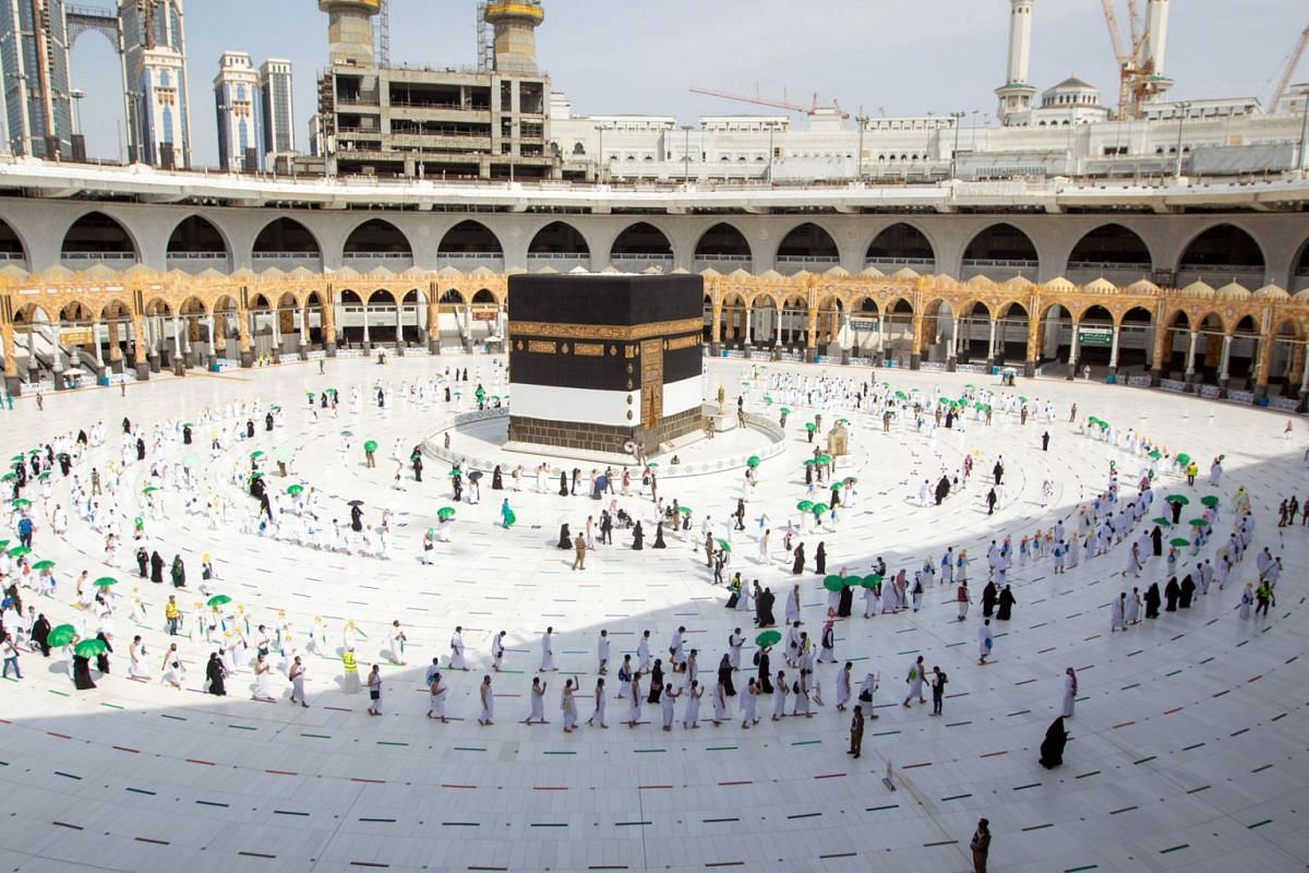 A handout photo made available by the Saudi Ministry of Hajj and Umrah shows Muslim pilgrims, wearing protective face masks, circling around the Kaaba at the Masjidil Haram, Islam's holiest site during the annual Hajj pilgrimage, in the holy city of