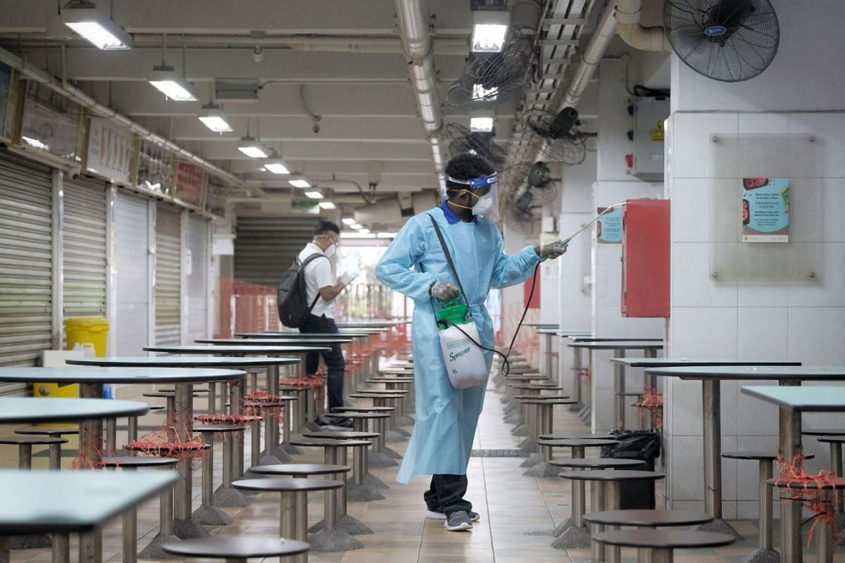Staff from a cleaning company disinfecting Hong Lim Market and Food Centre on, July 18, 2021.