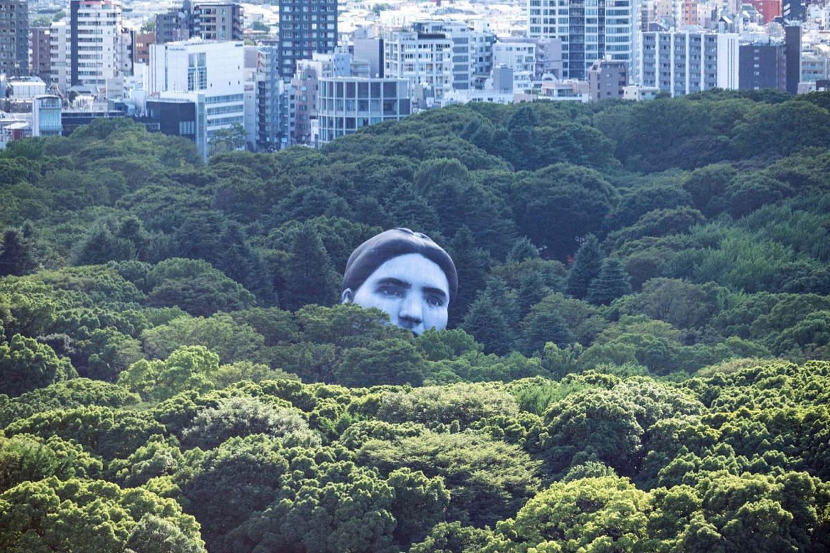 """A hot air balloon created by Japanese art group """"mé"""" pops up over the trees at Tokyo's Yoyogi Park on July 16, 2021, part of a project called """"Masayume"""" - a Japanese word for a dream that becomes reality."""