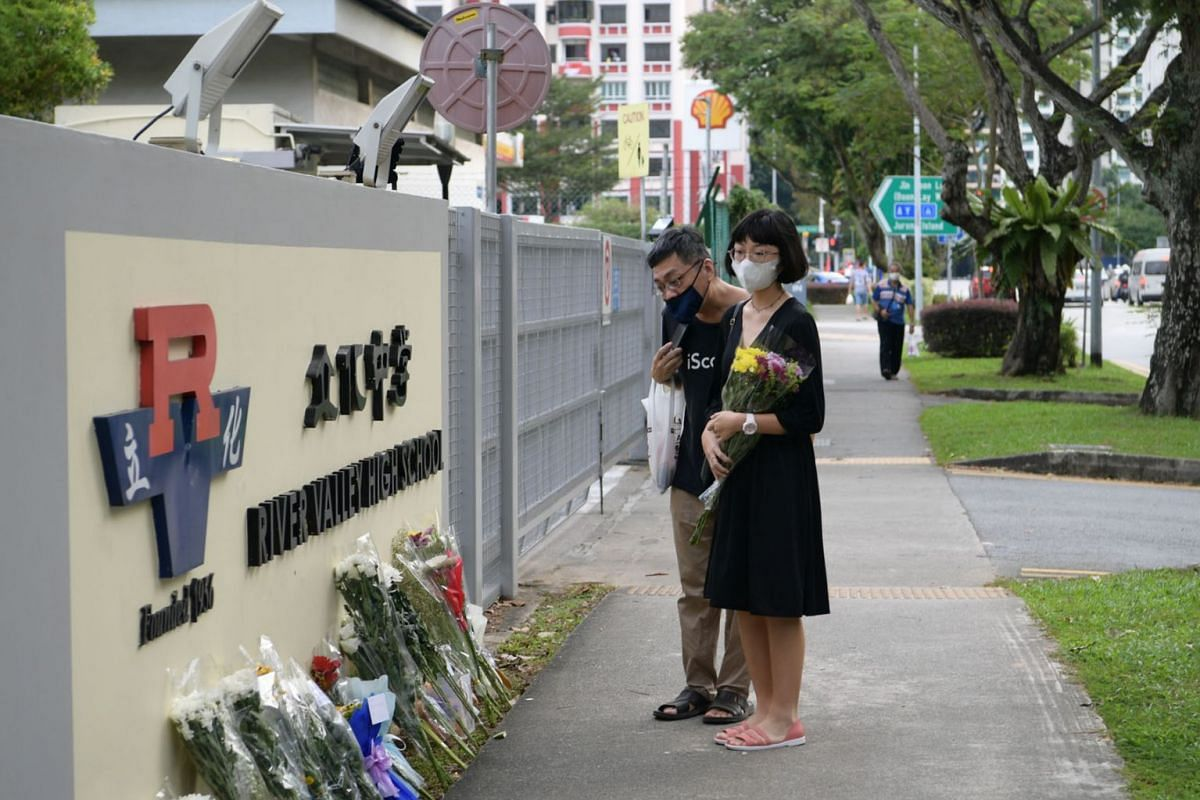 River Valley High School student Lim Xin Mei, 16, who is in Secondary 4, arriving at the school with a bouquet of flowers on July 20, 2021, in memory of the Secondary 1 student killed in school on Monday. Parents, alumni and residents living nearby p