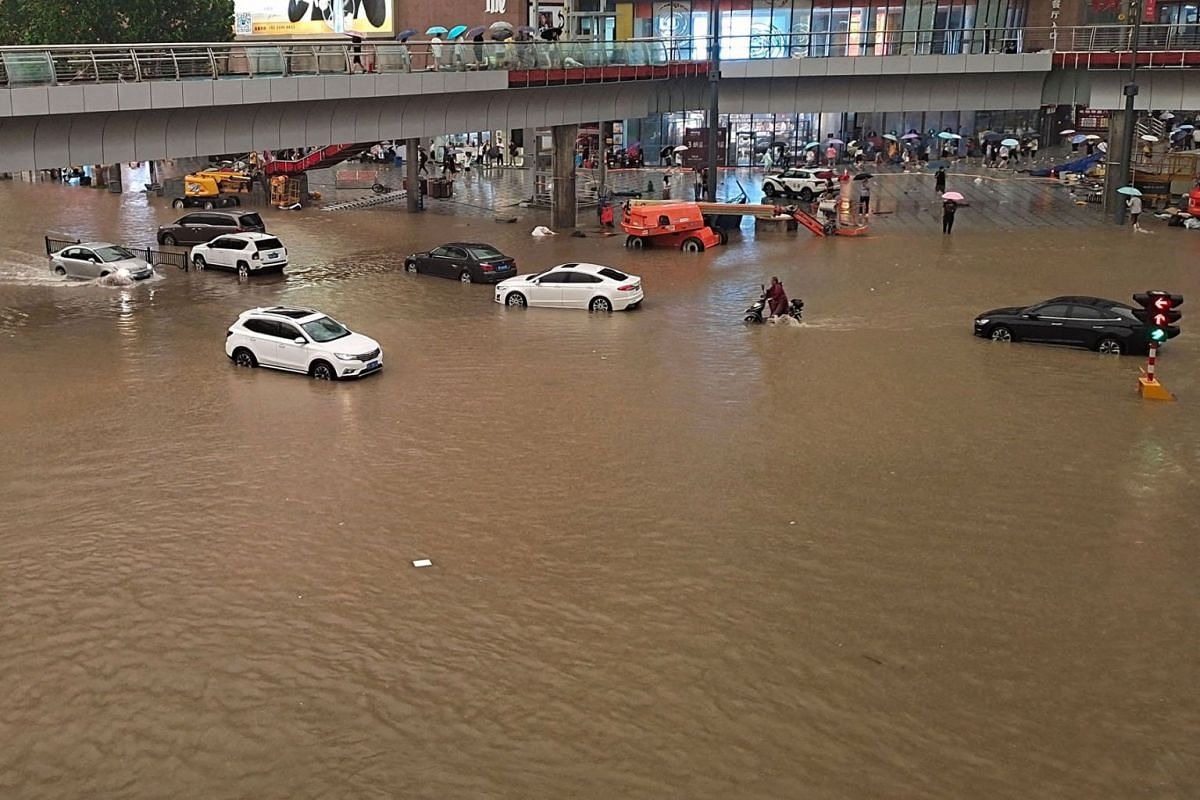 This photo taken on July 20, 2021 shows people wading through flood waters along a street following heavy rains in Zhengzhou in China's central Henan province.