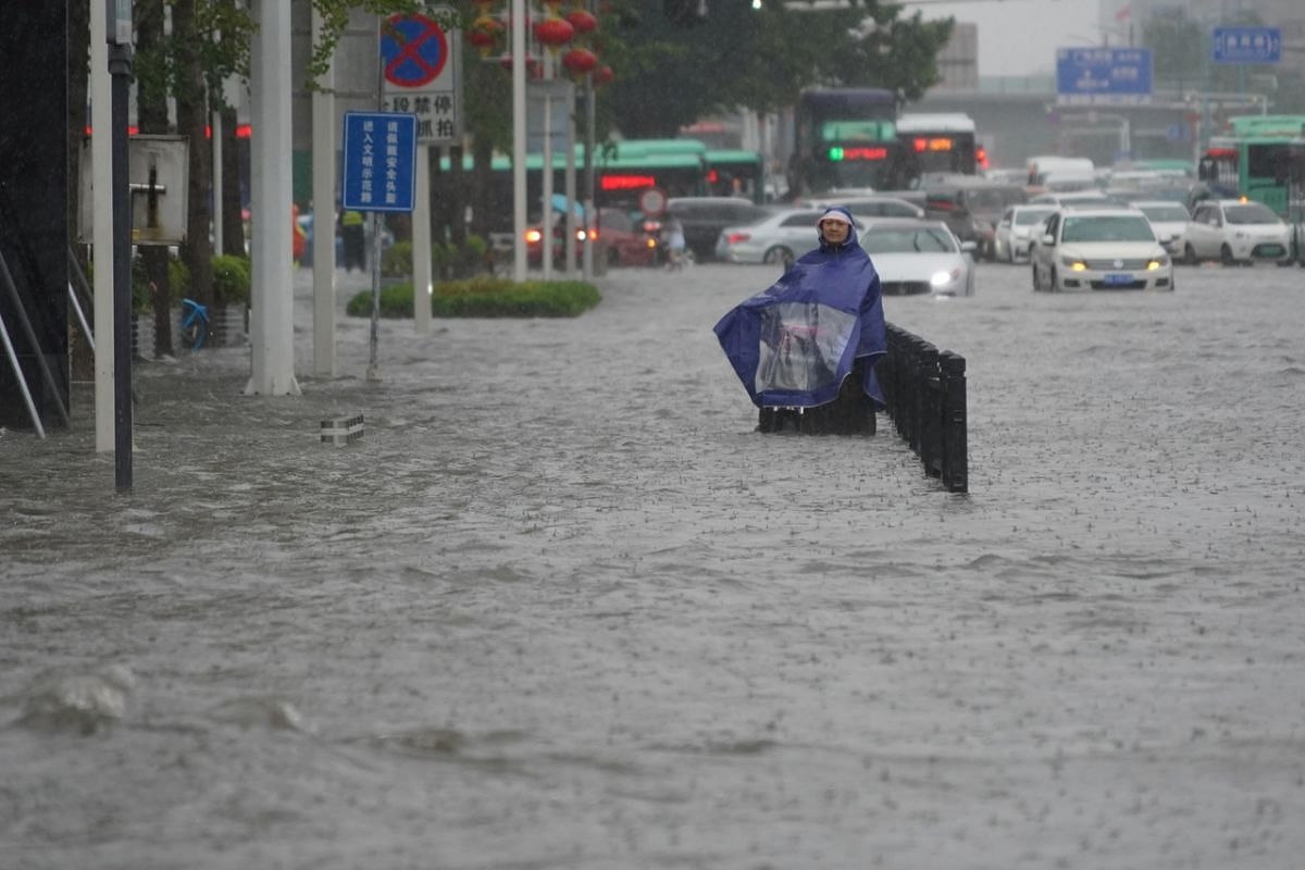 A resident wearing a rain cover stands on a flooded road in Zhengzhou, capital of central China's Henan province, on July 20, 2021.