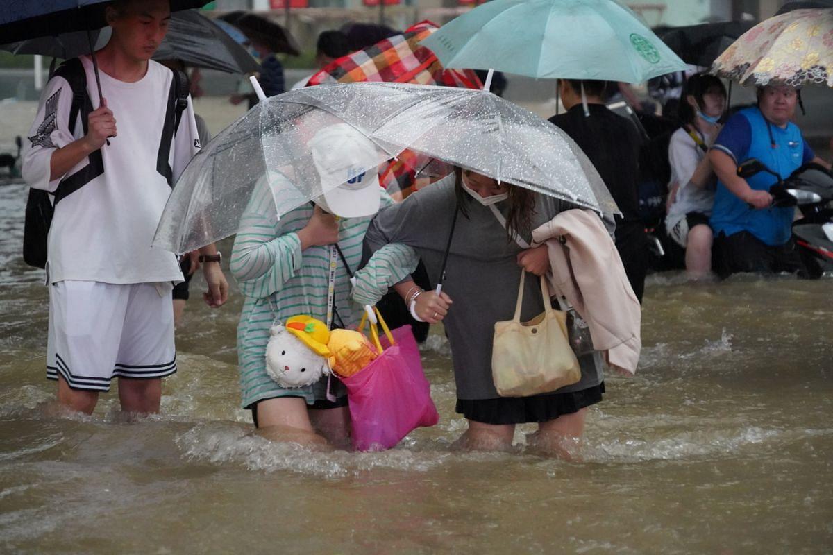 Residents, seeking shelter under umbrellas, wade through flood waters on July 20, 2021.