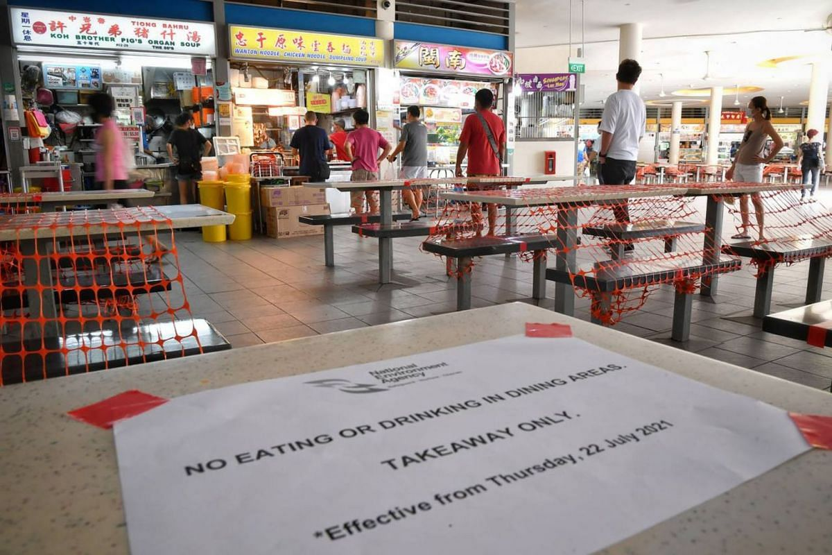 People observe safe distancing as they queue to buy food at Tiong Bahru Market on the first day of the dine-in ban as seen in a photo taken on July 22, 2021. Singapore reverted back to phase two (heightened alert), with tighter measures in place to c
