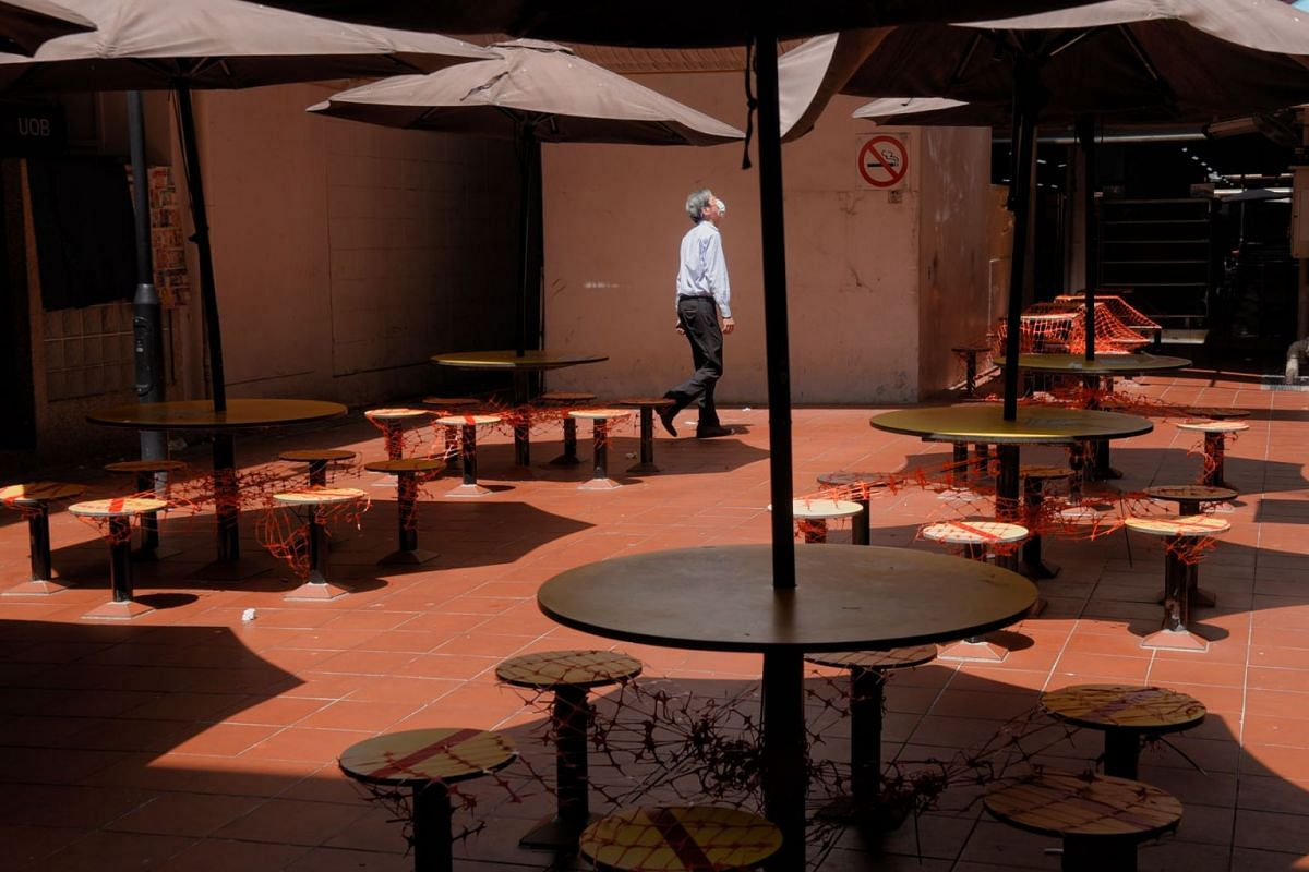 A man is seen walking by covered seats at People's Park Food Centre on 22 July, 2021.