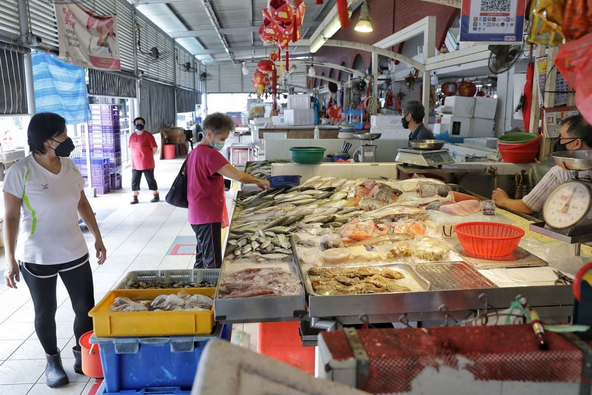 Fishmongers seeing low traffic and slow business at Kovan 209 Market and Food Centre on July 22, 2021. These fishmongers have undergone PCR testing, one of them as many as three times in four days, and returned to open their business (July 21) after