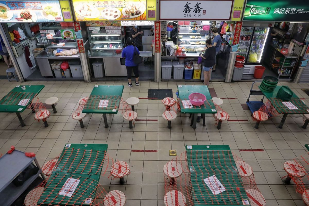 People ordering takeaways at Kovan 209 Market and Food Centre on July 22, 2021. In-dining is not allowed under these tightened Covid-19 measures.