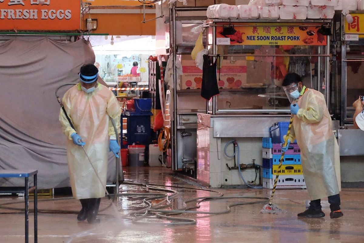 Workers carrying out deep cleaning and disinfecting works at Chong Pang Market & Food Centre in Yishun on July 21, 2021.