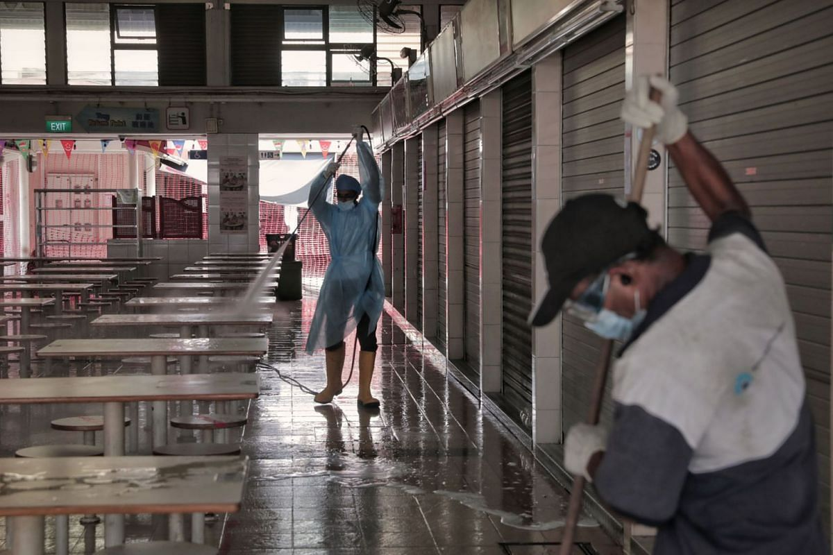 Workers carrying out deep cleaning and disinfecting works at Haig Road Market and Food Centre on July 21, 2021.
