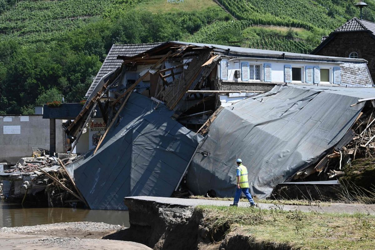 An emergency helper walks past a damaged house on a blocked road in Rech, Rhineland-Palatinate, western Germany, on July 21, 2021, after devastating floods hit the region.