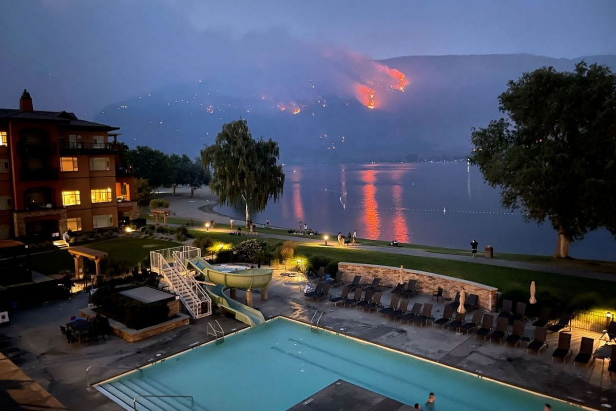 View of a beach resort as a wildfire burns on a hillside in Osoyoos, British Columbia, Canada, on July 20, 2021 in this still image taken from social media.