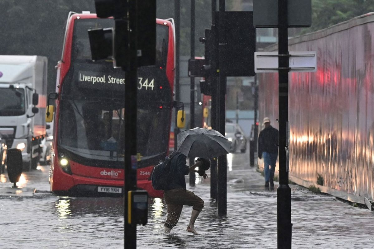 A pedestrian crosses through deep water on a flooded road in The Nine Elms district of London, Britain, on July 25, 2021, during heavy rain.