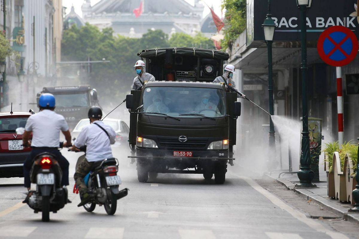 Soldiers from The High Command of Chemicals under Vietnam's Ministry of National Defence spray disinfectant throughout a street as a precaution against the coronavirus, in Hanoi, Vietnam, on July 26, 2021. Vietnam is facing a fourth Covid-19 wave.