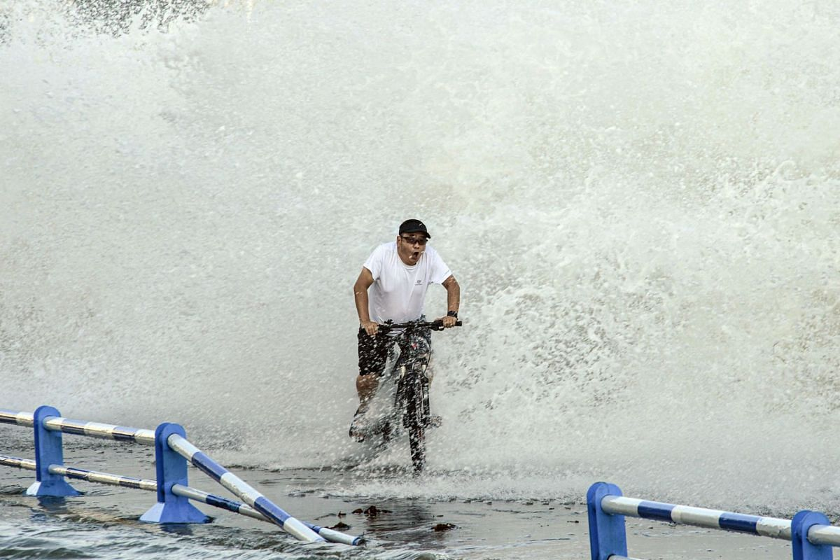 This photo taken on July 25, 2021 shows a man riding a bicycle as waves, caused by Typhoon In-Fa further down the Chinese coast, surge over a barrier along the seacoast in Qingdao in China's eastern Shandong province.
