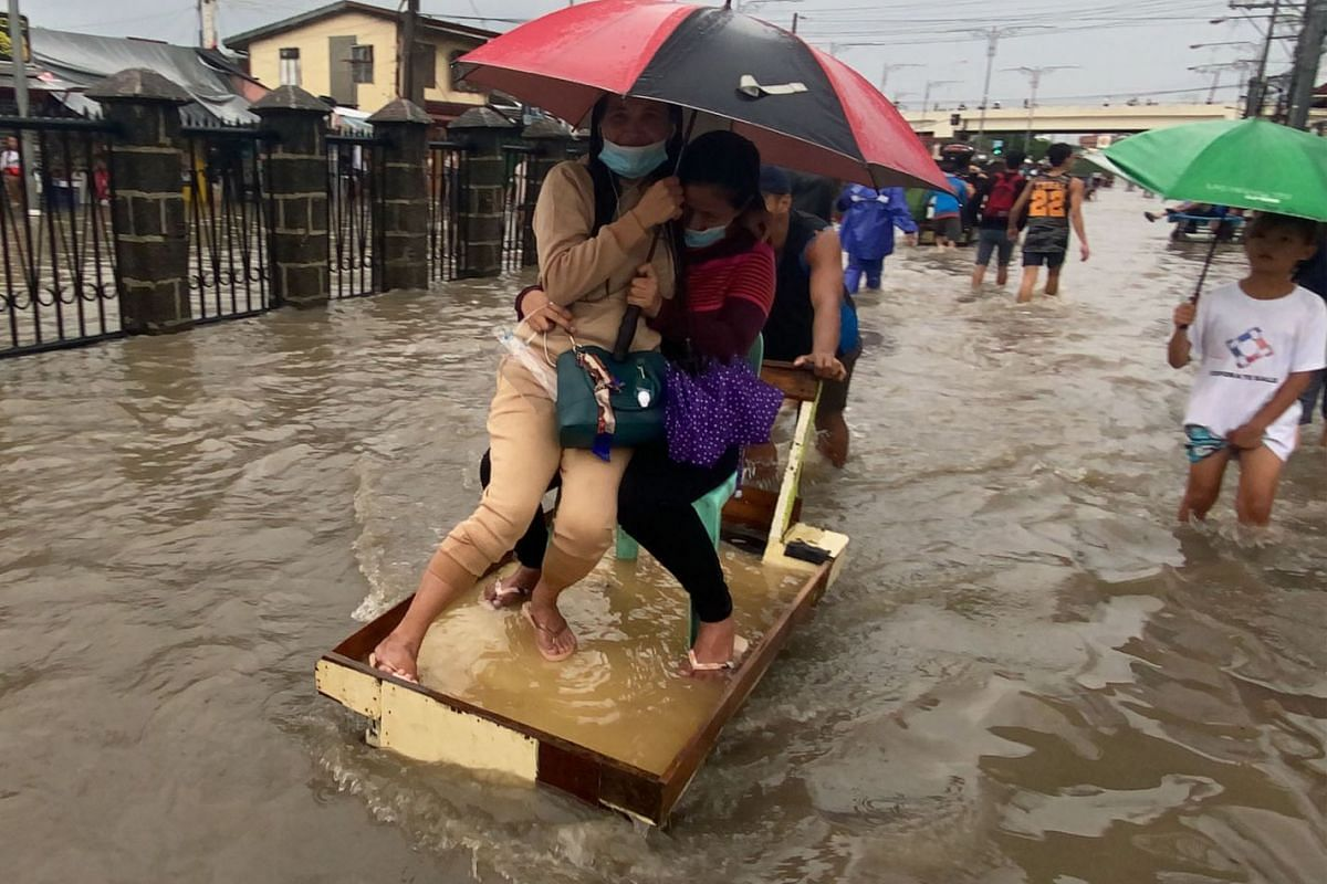 Filipinos ride a makeshift cart along a flooded road in Las Pinas city, Metro Manila, Philippines, on July 24, 2021.