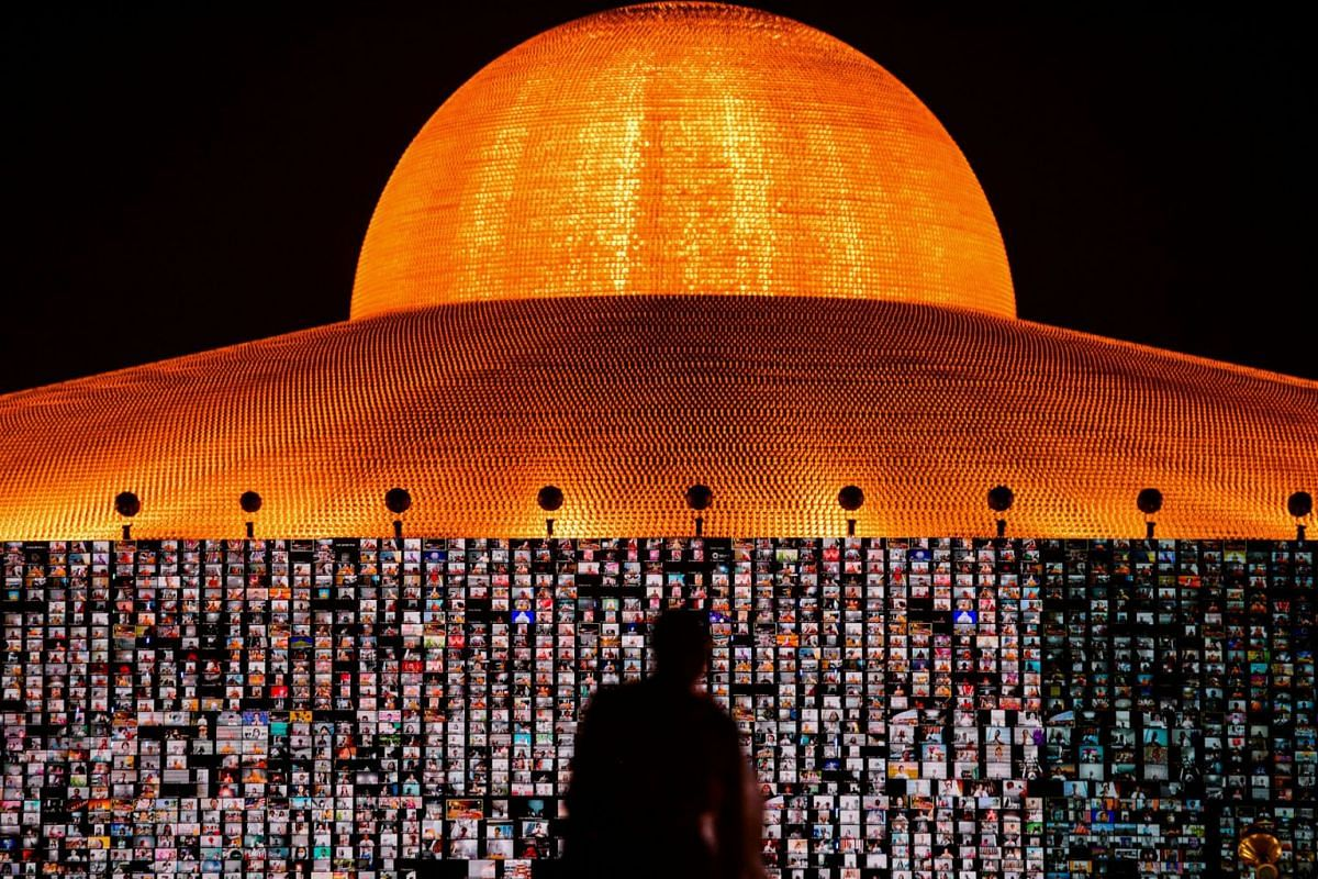 People pray as screens show devotees gathering via the Zoom application during a ceremony to commemorate the Buddhist Lent Day at the Wat Phra Dhammakaya temple, amid the coronavirus disease outbreaks, in Pathum Thani province, Thailand, on July 24,