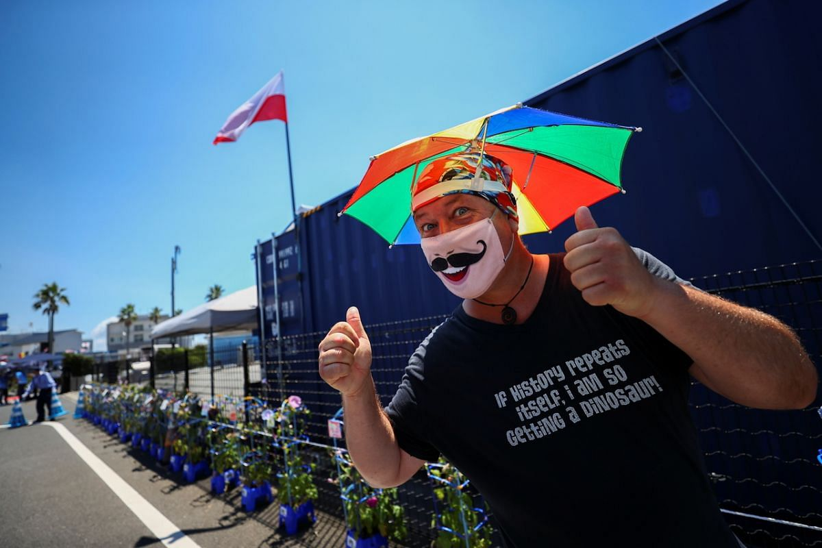 A man wearing a protective face mask flashes thumbs up at the Tokyo 2020 Olympic Games sailing venue in Enoshima Yacht Harbour, on July 22, 2021.