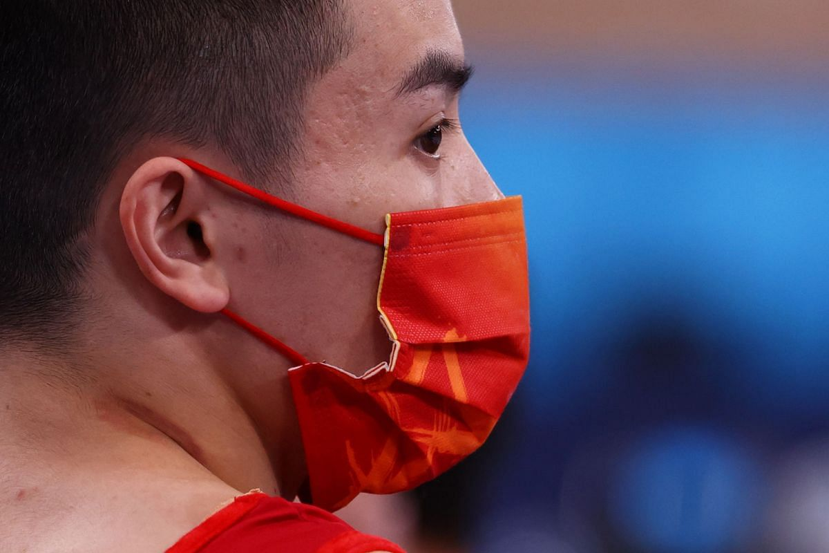 Chinese gymnast Lin Chaopan wears a mask after performing on the pommel horse, on July 24, 2021.