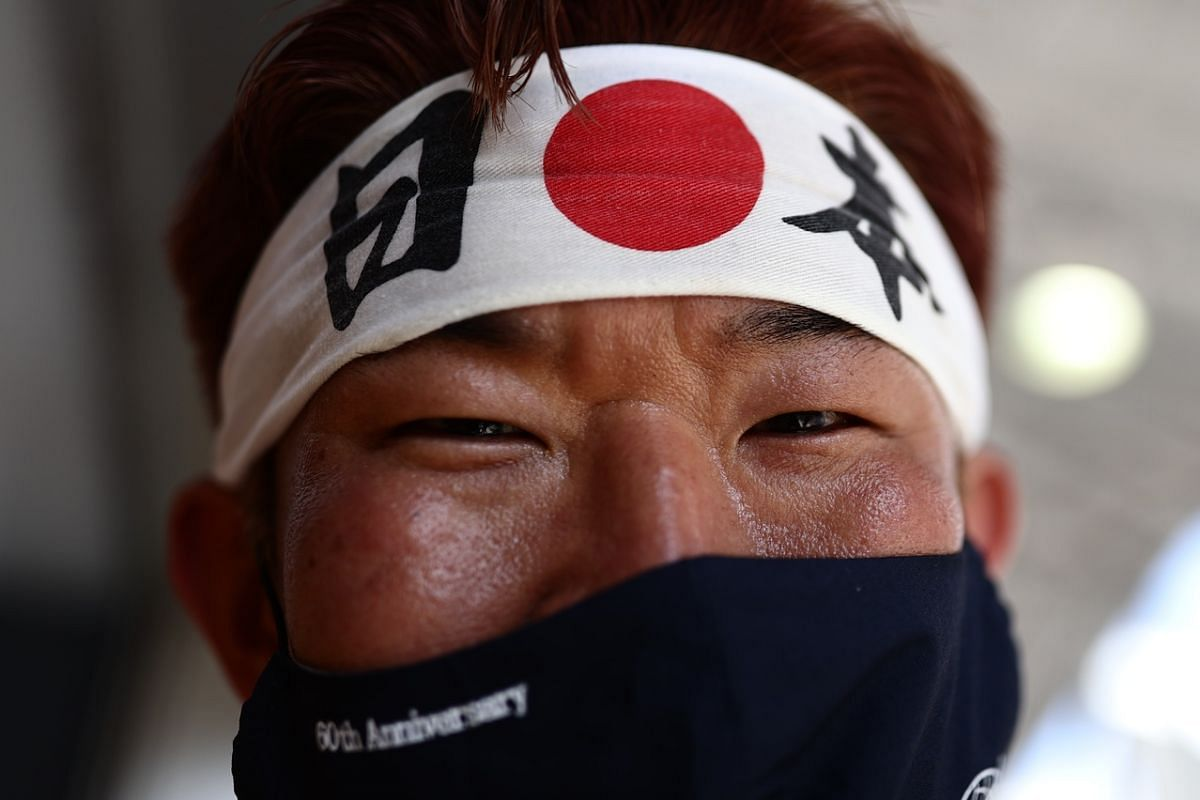 A staff member poses for a photo at the finish of the Women's Road Race in Tokyo, on July 25, 2021.