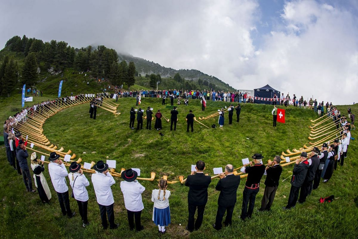 A group of 120 Alphorn players take part in a performance during the 20th international alphorn festival in Nendaz, Switzerland, July 25,  2021.