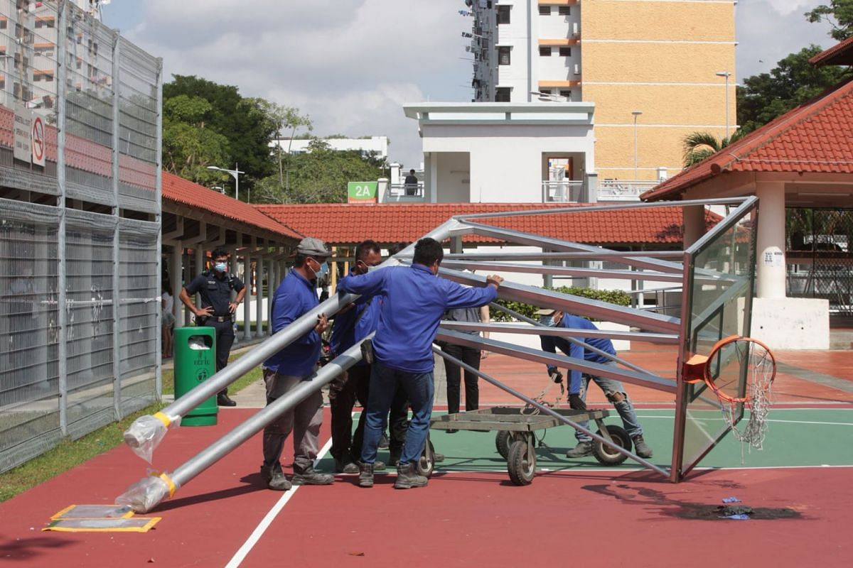 Workers removing the fallen basketball structure near Block 18 Bedok South Road on July 27, 2021. A 17-year-old died after a basketball backboard structure in Bedok fell on him on Monday (July 26) night.