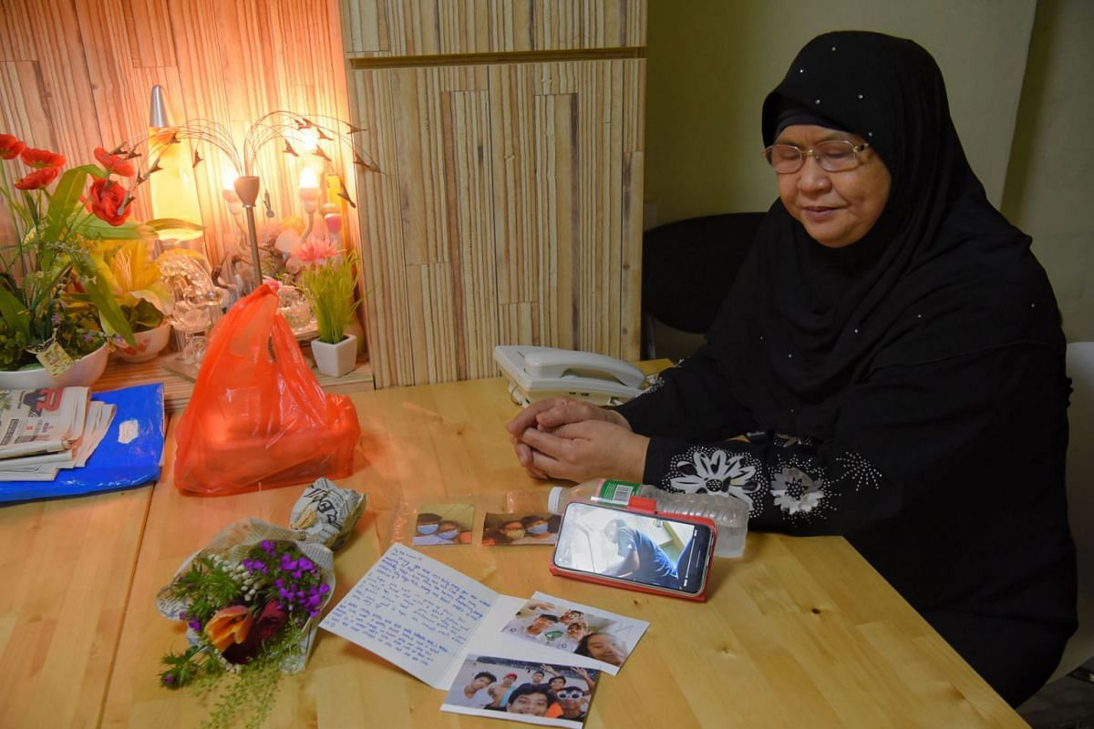 A photo taken on July 28, 2021, shows Madam Rahimah Lee Abdullah, 62, with some pictures of her son Muhd Ridwan, 17, who died on Monday night after the backboard structure of a basketball hoop fell on him.