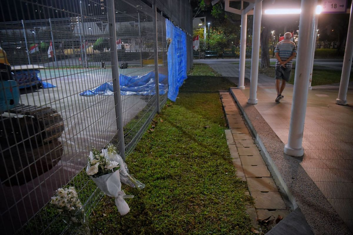 A photo taken on July 28, 2021, shows four small bouquet of flowers at the basketball court where 17-year-old Muhd Ridwan died on Monday.