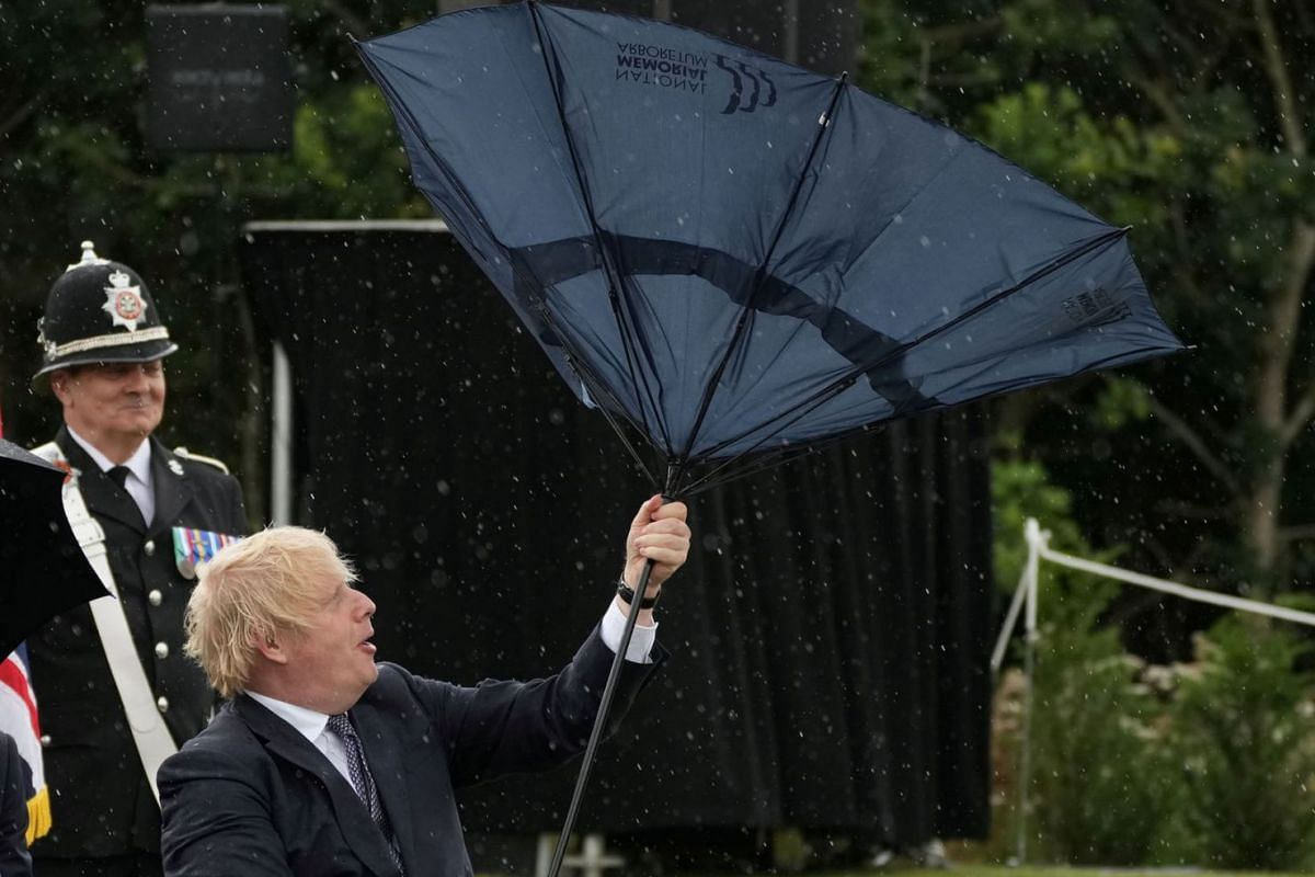 Britain's Prime Minister Boris Johnson struggles with an umbrella during a visit to the National Memorial Arboretum at Alrewas, Staffordshire, Britain, July 28, 2021.