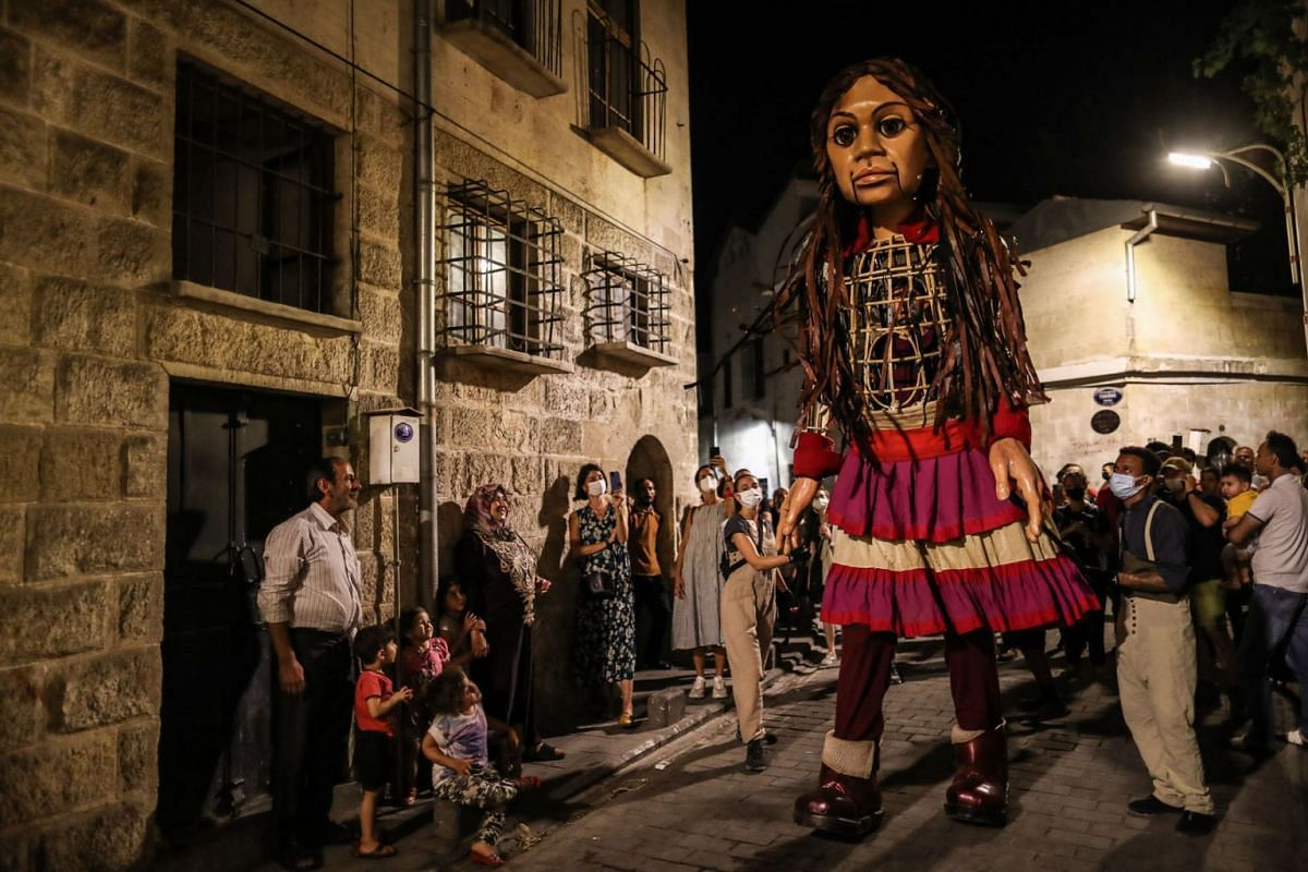 A giant puppet of a young refugee girl Amal walks on street with Syrian refugees children in Gaziantep, Turkey, July 27, 2021.