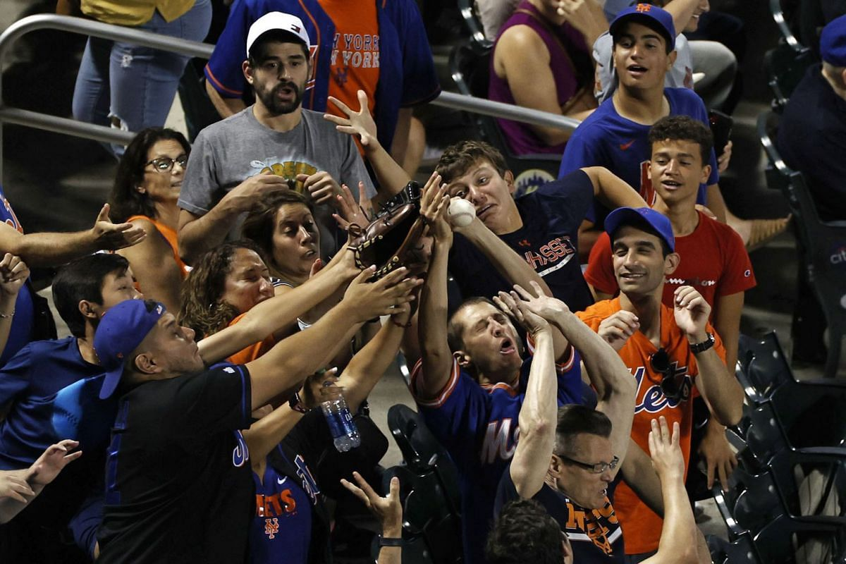 Fans attempt to catch a foul ball during the fifth inning between the Atlanta Braves and the New York Mets at Citi Field on July 28, 2021 in New York City.