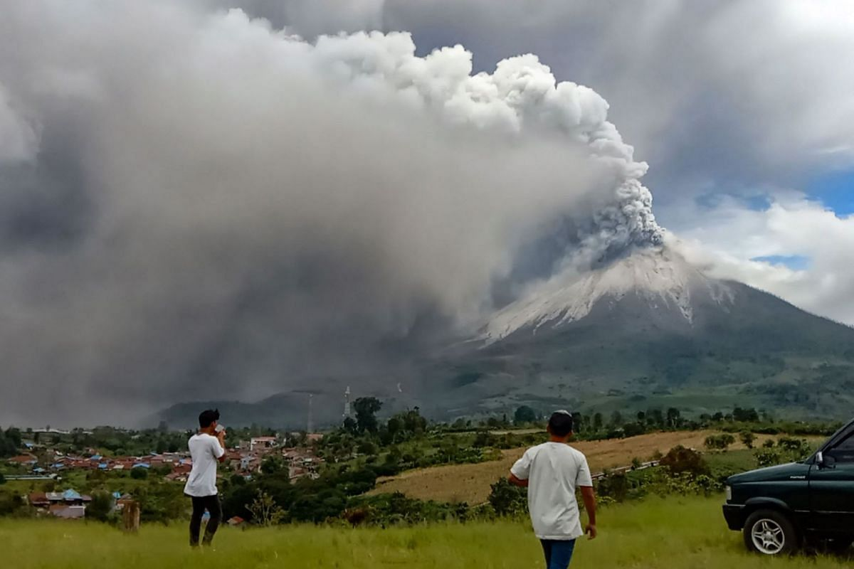 People look on as Mount Sinabung erupts spewing a massive column of smoke and ash as seen from Karo, North Sumatra, Indonesia, on July 28, 2021.
