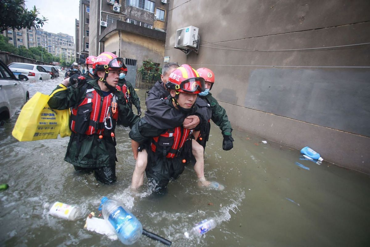 This photo taken on July 28, 2021 shows rescuers evacuating residents at a flooded area in Yangzhou, in China's eastern Jiangsu province, after heavy rains brought by the passage of Typhoon In-Fa inundated the eastern coast of China.