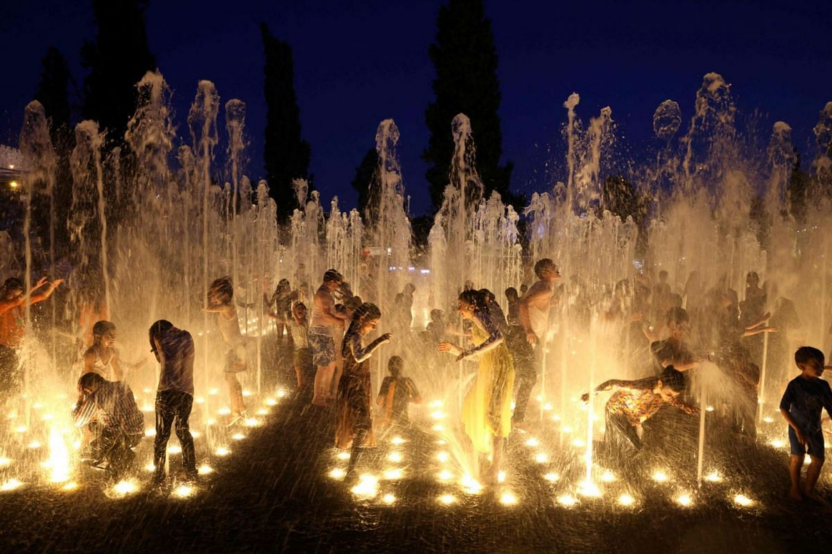Youths and children enjoy a water fountain in the heart of Jerusalem on July 28, 2021.