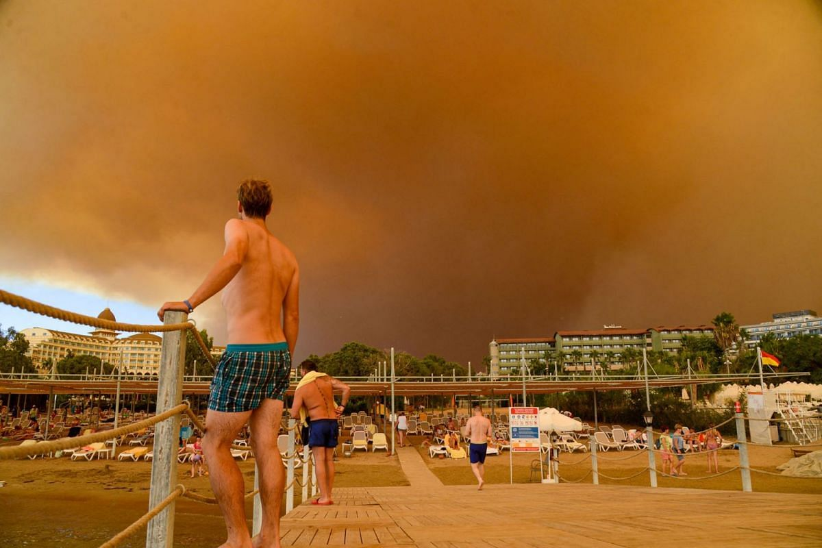 Dark smoke drifts over a hotel complex during a massive forest fire which engulfed a Mediterranean resort region on Turkey's southern coast near the town of Manavgat, on July 29, 2021.