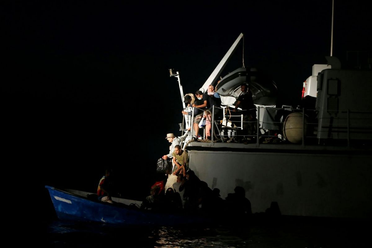 Migrants return to their wooden boat from a Libyan Coast Guard vessel after German NGO migrant rescue ship Sea-Watch 3 took over a rescue operation in the Maltese search and rescue zone in international waters off the coast of Libya, in the western M