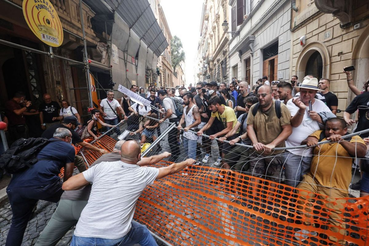 Protesters try to tear down a barricade during a demonstration against the Green Pass proof of vaccination certificate, in Rome, Italy, July 27, 2021.