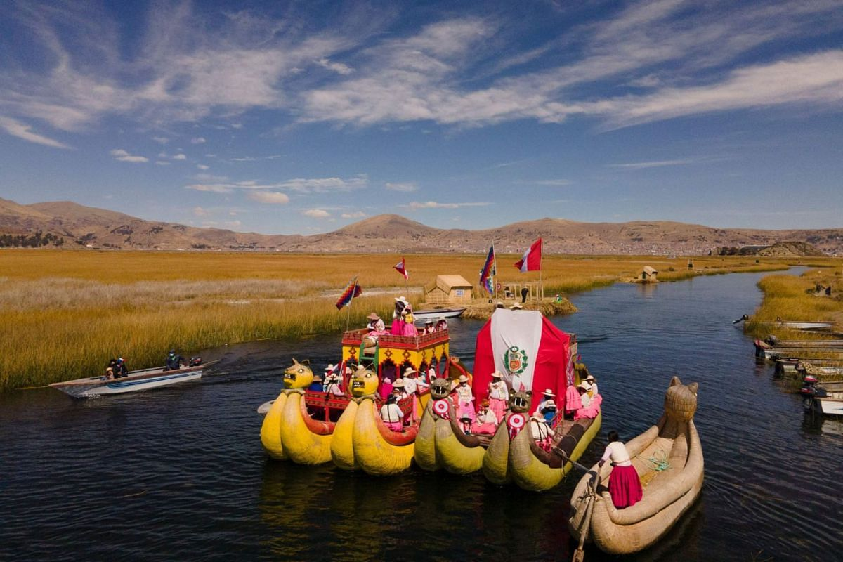 Artisians of the Qota Tika association march on boats with the Peruvian flag during a celebration in commemoration of Peru's bicentennial of the Indenpendence Day, near Lake Titicaca in Puno, Peru, on July 28, 2021.