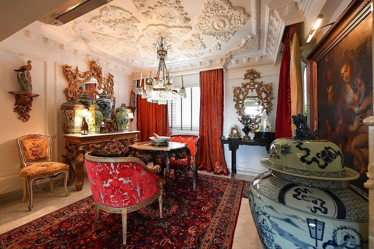 Artist and art collector Johann M. Fauzi (above) favours opulence in his interior design, as can be seen in a red and gold room (below) in his flat, which features gilded mirrors, a lavish chandelier and a Turkish rug.