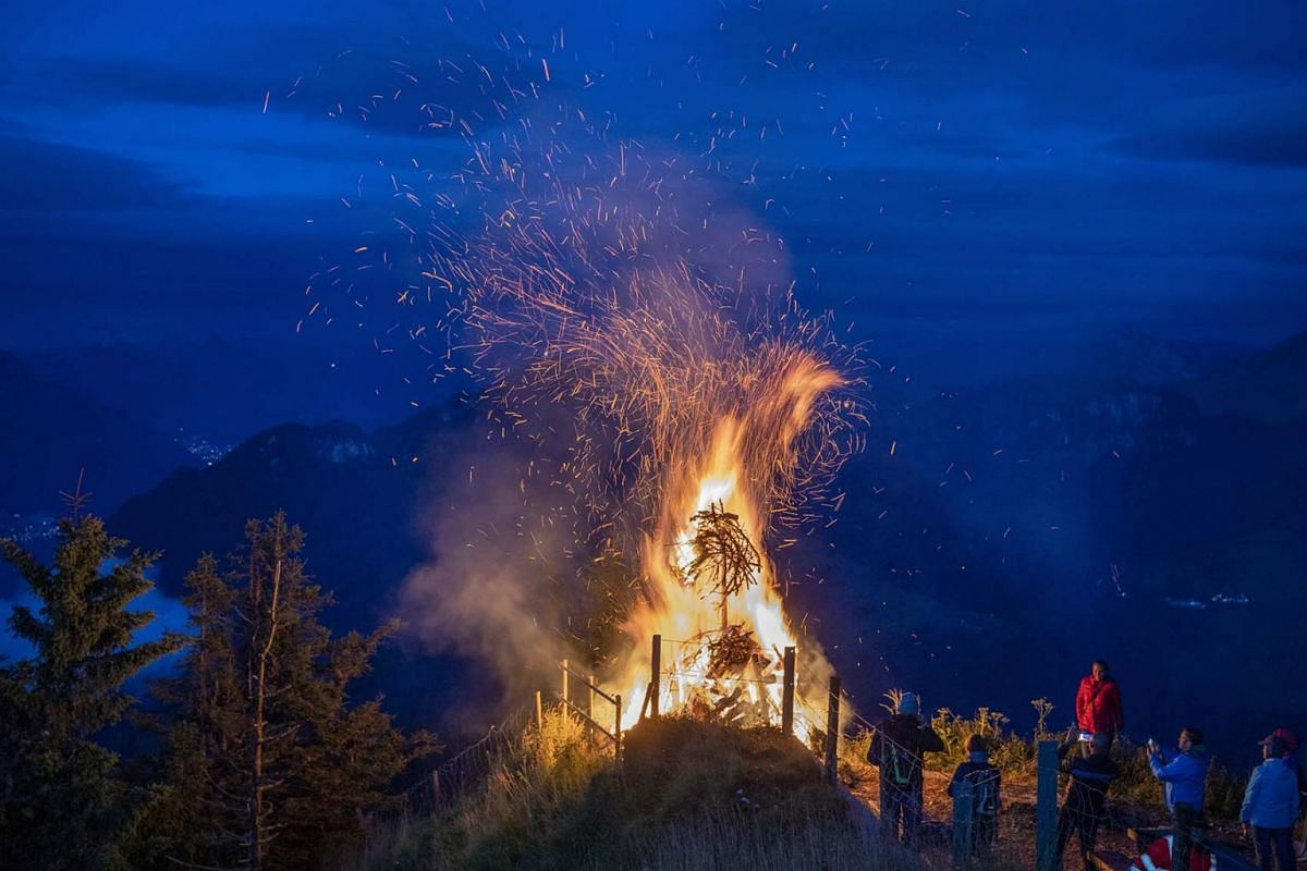 A traditional high altitude bonfire burns into the evening sky on the occasion of the Swiss National Day on Stanserhorn mountain, near Stans, Switzerland, Aug 1, 2021.