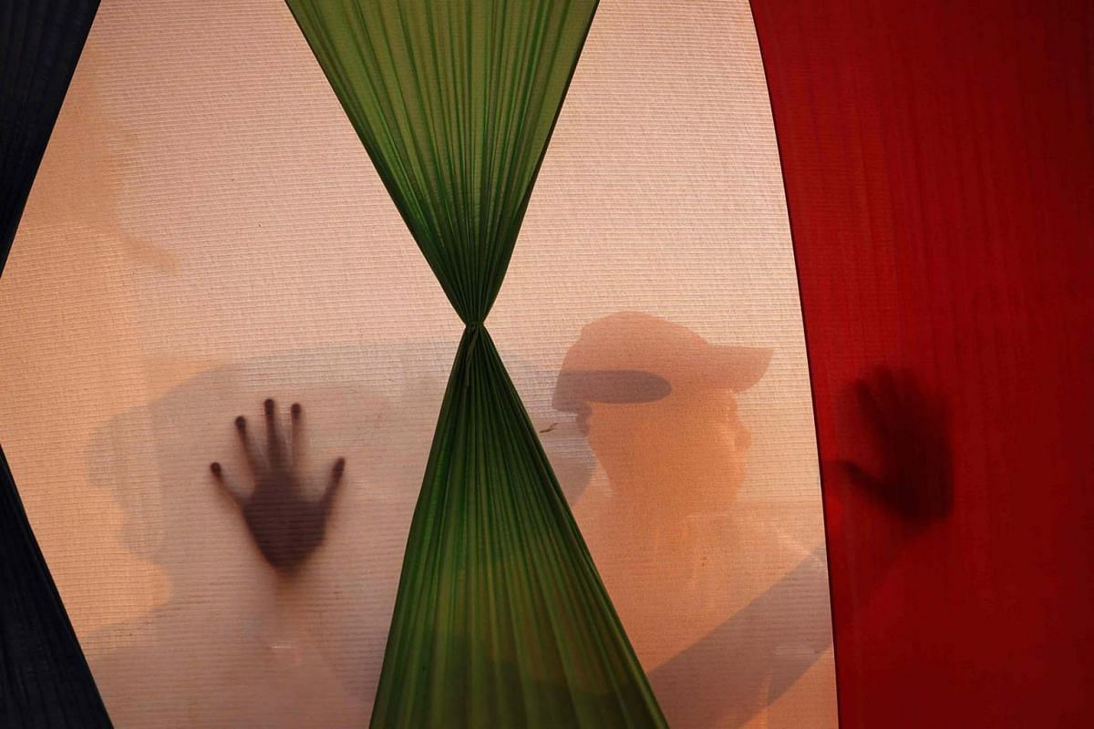 A Palestinian child is silhouetted behind a palestinine flag in a tent in Gaza City on Aug 1, 2021.