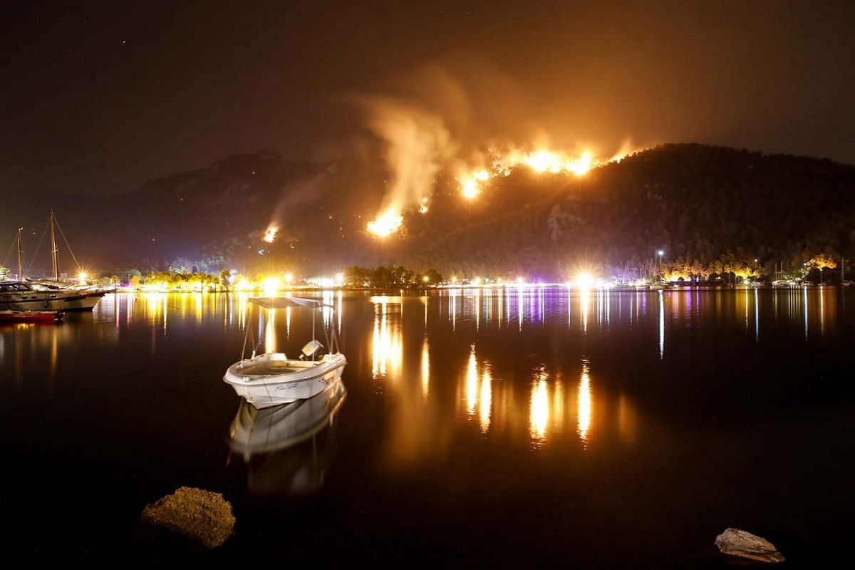 Flames and smoke rises from mountains in Orhaniye village near Marmaris, Turkey, Aug 4, 2021.
