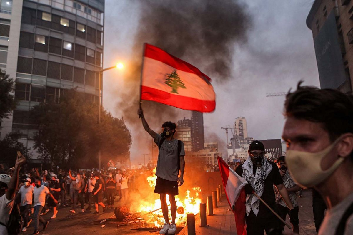 A protester stands with a Lebanese national flag during clashes with army and security forces near the Lebanese parliament headquarters in the centre of the capital Beirut on Aug 4, 2021,  the first anniversary of the blast that ravaged the port and