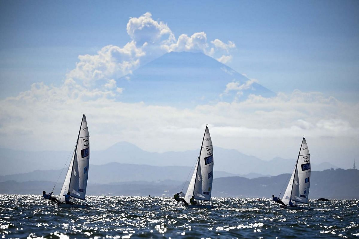 (from left) Japan's Ai Yoshida and Miho Yoshioka, Britain's Hannah Mills and Eilidh Mcintyre and France's Aloise Retornaz and France's Camille Lecointre sail past Mount Fuji during the women's two-person dinghy 470 medal race during the Tokyo 2020 Ol